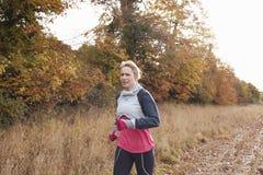 跑在秋天领域附近的成熟妇女 免版税库存图片