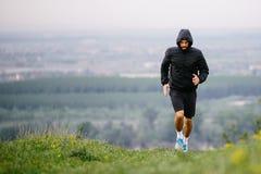 跑在秋天,冬天早晨期间的运动年轻人 免版税库存照片