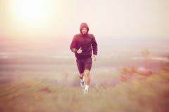 跑在秋天,冬天早晨期间的运动年轻人 免版税库存图片