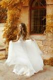 跑在秋天p的白色婚礼礼服的美丽的新娘妇女 免版税库存照片