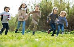 跑在种族的小组孩子户外 免版税库存图片