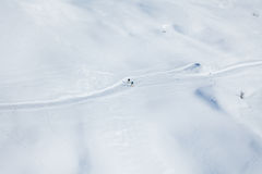 跑在积雪覆盖的山的两个滑雪者 库存图片