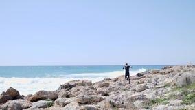 跑在穿黑服装的一个多岩石的海滩的岩石的白种人运动人 影视素材