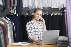 跑在线在电话的时装业的女实业家 库存照片