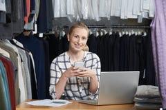 跑在线衣物在膝上型计算机的企业工作的妇女画象 免版税库存照片