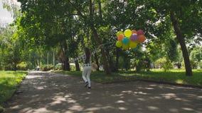 跑在绿色公园和举行五颜六色的气球的女孩后面神色 股票录像