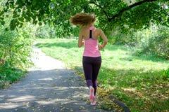 跑在绿色公园的美丽的少妇在晴朗的夏日 免版税库存图片