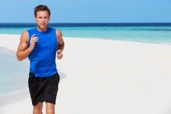 跑在美丽的海滩的人 免版税库存照片