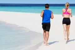 跑在美丽的海滩的夫妇背面图  库存图片