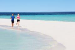 跑在美丽的海滩的夫妇 免版税库存图片