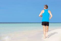 跑在美丽的海滩的老人 库存照片