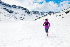 跑在美丽的激动人心的土地的愉快的妇女冬天足迹 免版税库存照片