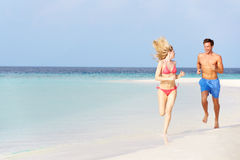 跑在美丽的热带海滩的浪漫夫妇 免版税库存照片