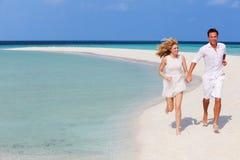 跑在美丽的热带海滩的浪漫夫妇 免版税库存图片