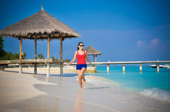 跑在美丽的热带海滩的年轻亚裔看的妇女画象在马尔代夫 库存图片