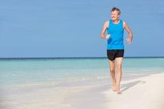 跑在美丽的海滩的老人 图库摄影