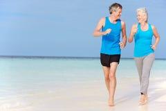 跑在美丽的海滩的资深夫妇 免版税库存图片