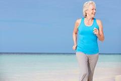 跑在美丽的海滩的资深妇女 免版税库存图片
