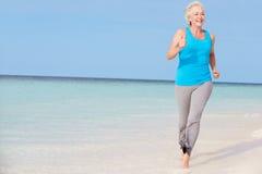 跑在美丽的海滩的资深妇女 免版税库存照片