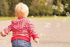 跑在肥皂bublles中的逗人喜爱的小孩在公园 回到视图 免版税库存照片