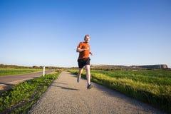 跑在自然的运动年轻人 健康生活方式 免版税库存图片