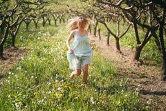 跑在花中的微笑的妇女 免版税库存图片