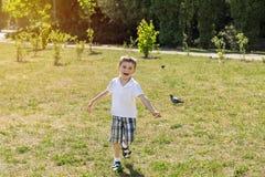 跑在草坪的愉快的小男孩在城市公园在一个夏天 库存照片