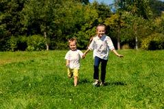 跑在草的女孩和男孩 免版税库存照片