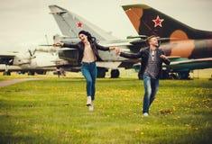 跑在草的年轻愉快的夫妇 免版税库存照片