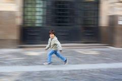 跑在街道上的男孩 免版税库存照片
