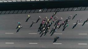 跑在街道上的马拉松 跟随的小组运动员慢动作 顶视图 股票视频