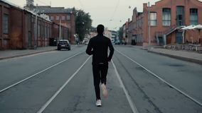 跑在街道中间的运动员 背景射击 慢的行动 在电车轨道之间的后面遥远的看法 影视素材
