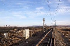 跑在被烧的农田之间的铁路线 免版税图库摄影