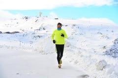 跑在足迹赛跑者坚硬锻炼的雪山的年轻健康体育人在冬天 库存照片