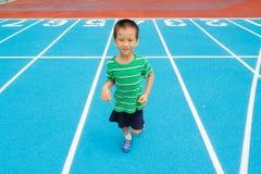 跑在跑马场的男孩 库存图片