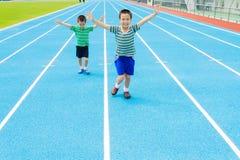 跑在跑马场的男孩 免版税库存照片