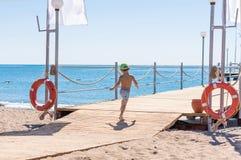 跑在路的愉快的男婴在海边附近 免版税图库摄影