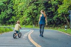 跑在路的运动的妇女在日出 儿子去平衡自行车 健身和锻炼健康概念 免版税库存照片