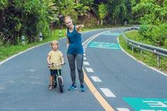 跑在路的运动的妇女在日出 儿子去平衡自行车 健身和锻炼健康概念 库存照片