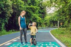 跑在路的运动的妇女在日出 儿子去平衡自行车 健身和锻炼健康概念 免版税库存图片
