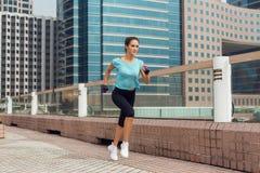 跑在路面的可爱的运动的少妇 免版税图库摄影