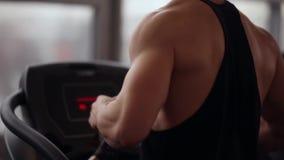 跑在踏车的一个坚强的爱好健美者的后面和侧视图,当解决在体育俱乐部时 健康生活方式 股票录像