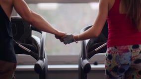 跑在踏车的一对运动的夫妇的后面看法握手 接近的现有量 解决在健身房 股票视频