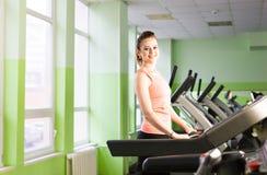 跑在踏车的健身女孩 有肌肉腿的妇女在健身房 免版税库存照片