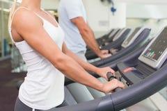 跑在踏车的夫妇的侧视图中间部分在健身房 库存图片