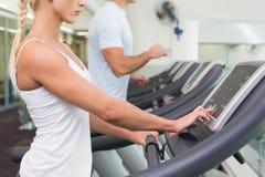 跑在踏车的夫妇的侧视图中间部分在健身房 免版税库存图片