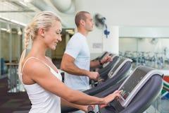 跑在踏车的夫妇的侧视图中间部分在健身房 免版税库存照片