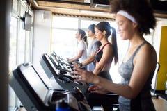 跑在踏车的愉快的适合的人民在健身健身俱乐部 库存照片