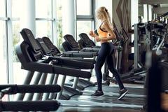 跑在踏车的运动白肤金发的妇女在健身房 免版税库存图片