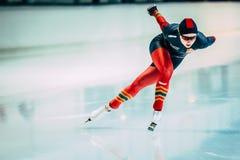 跑在轨道附近溜冰场的年轻运动员速度溜冰者 免版税库存图片
